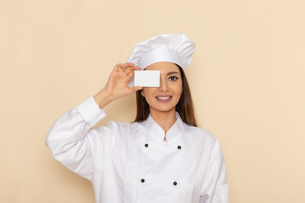 Widok z przodu młodej kobiety kucharki w białym garniturze kucharza trzymając kartę z uśmiechem na jasnobiałej ścianie