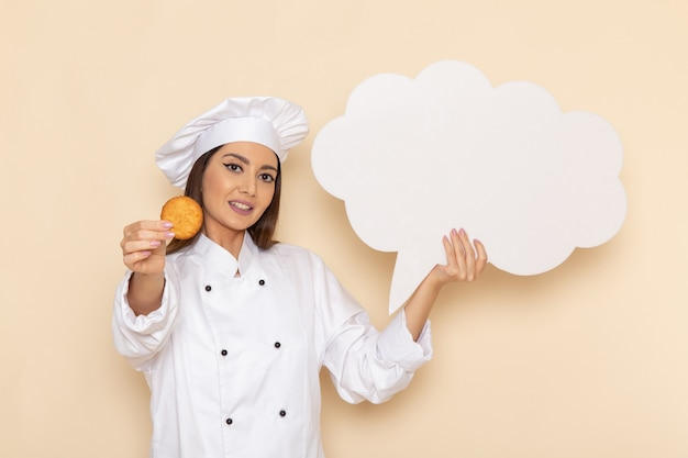Widok z przodu młodej kobiety kucharki w białym garniturze, trzymając ciasteczka i biały znak na jasnobiałej ścianie