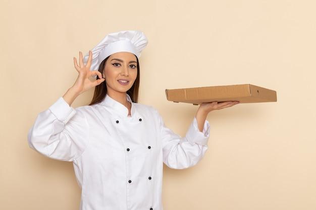 Widok z przodu młodej kobiety kucharki w białym garniturze, trzymając pudełko z jedzeniem z uśmiechem na jasnobiałej ścianie