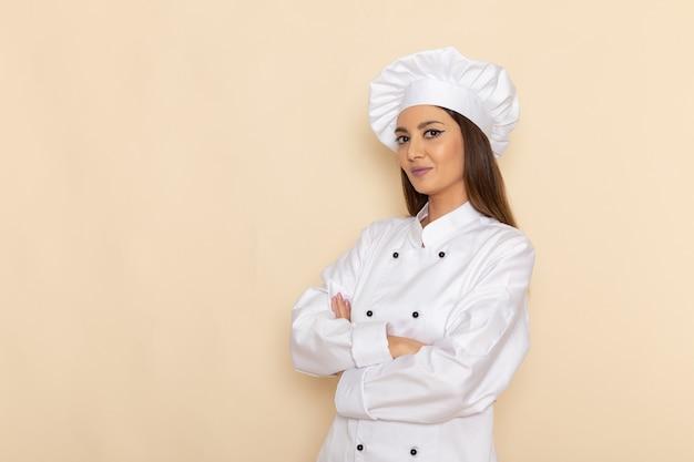 Widok z przodu młodej kobiety kucharki w białym garniturze z uśmiechem na jasnobiałej ścianie