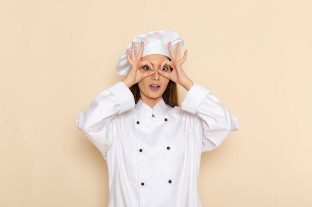 Widok z przodu młodej kobiety kucharz w białym garniturze na jasnobiałej ścianie