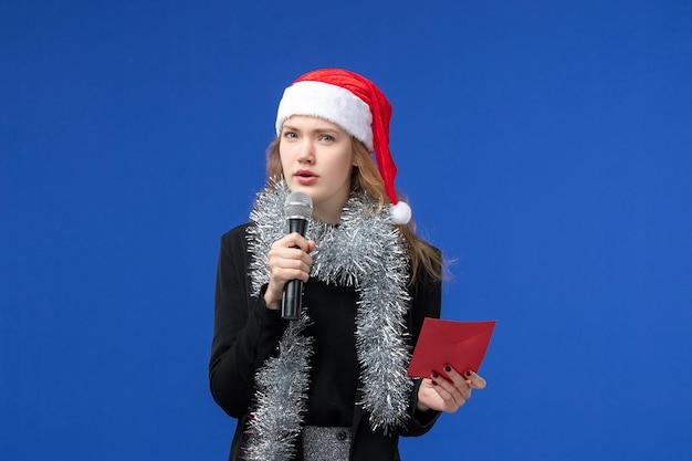 Widok z przodu młodej kobiety na imprezie karaoke z kopertą na niebieskiej ścianie