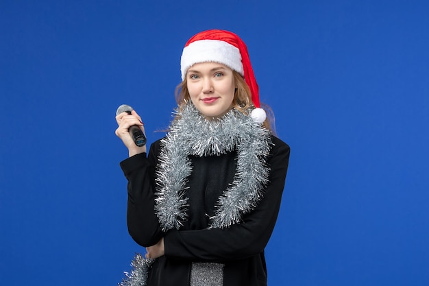 Widok z przodu młodej kobiety na noworocznej imprezie karaoke na niebieskiej ścianie