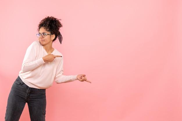Widok z przodu młodej kobiety na różowej ścianie