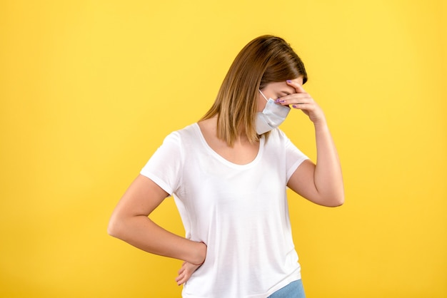 Widok z przodu młodej kobiety podkreślił w masce na żółtej ścianie