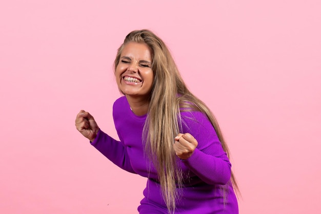 Widok z przodu młodej kobiety pozującej radośnie w pięknej fioletowej sukience na różowej ścianie