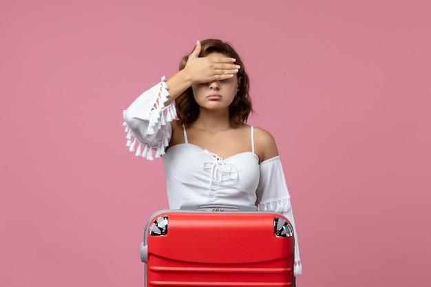 Widok z przodu młodej kobiety pozującej z czerwoną torbą na jasnoróżowej ścianie