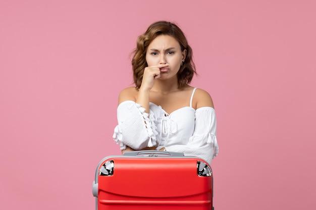 Widok z przodu młodej kobiety pozującej z czerwoną torbą wakacyjną na różowej ścianie