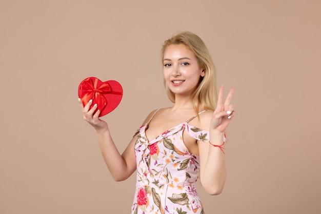 Widok z przodu młodej kobiety pozującej z prezentem w kształcie czerwonego serca na brązowej ścianie