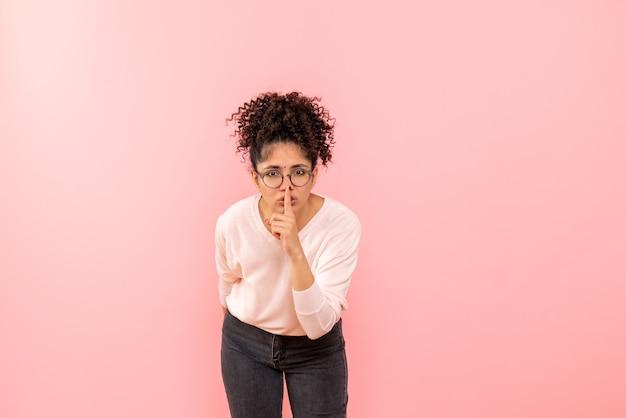 Widok z przodu młodej kobiety proszącej o milczenie na różowej ścianie