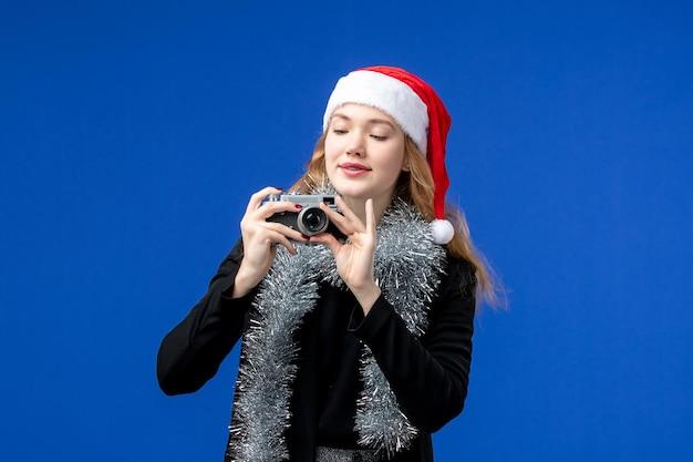Widok z przodu młodej kobiety robiącej zdjęcie aparatem na niebieskiej ścianie