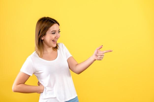 Widok z przodu młodej kobiety rozmawiającej z kimś na żółtej ścianie