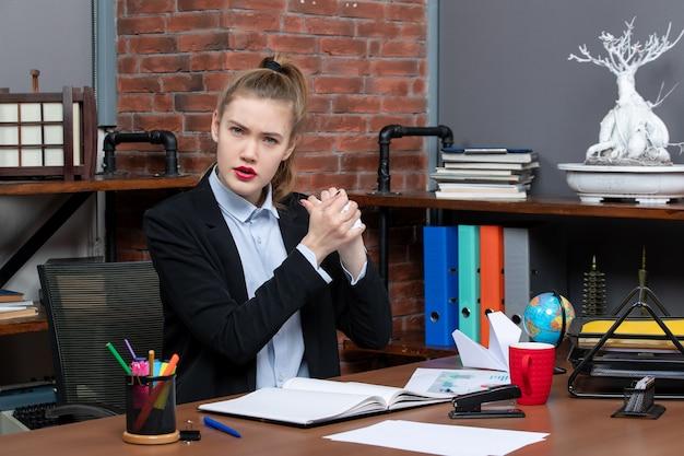 Widok z przodu młodej kobiety siedzącej przy stole i trzymającej owinięty papier w biurze