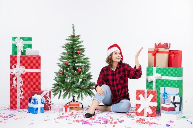 Widok z przodu młodej kobiety siedzącej wokół prezentów świątecznych i choinki na białej ścianie