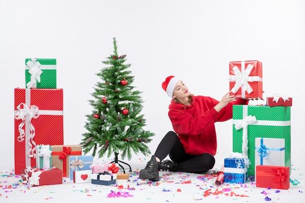 Widok z przodu młodej kobiety siedzącej wokół prezentów wakacyjnych na białej ścianie