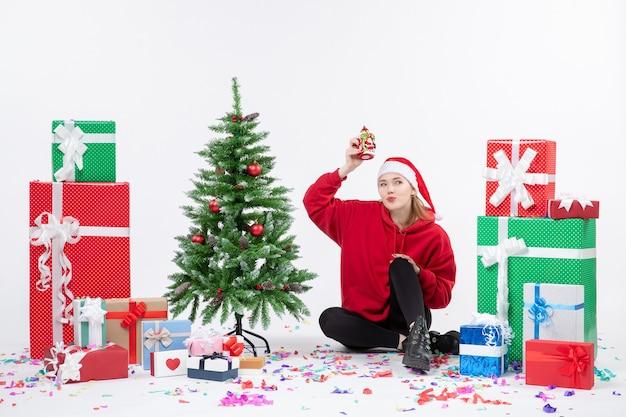 Widok z przodu młodej kobiety siedzącej wokół prezentów wakacyjnych, trzymając coś na białej ścianie