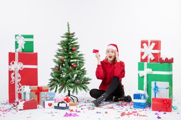 Widok z przodu młodej kobiety siedzącej wokół przedstawia trzymając czerwoną kartę bankową na białej ścianie