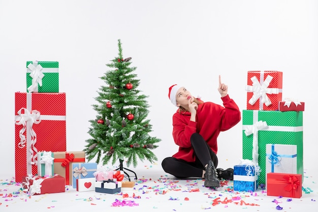 Widok z przodu młodej kobiety siedzącej wokół różnych świątecznych prezentów na białej ścianie