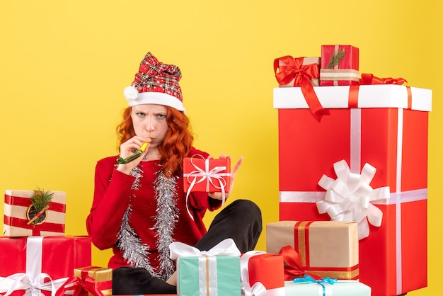 Widok z przodu młodej kobiety siedzącej wokół różnych świątecznych prezentów na żółtej ścianie