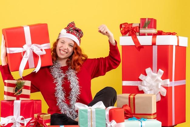 Widok z przodu młodej kobiety siedzącej wokół świątecznych prezentów na żółtej ścianie