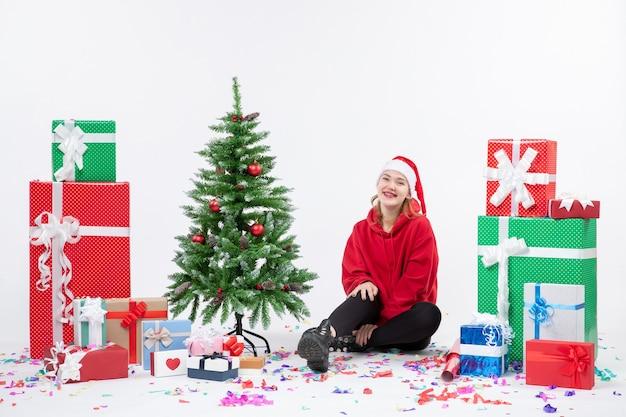 Widok z przodu młodej kobiety siedzącej wokół świątecznych prezentów, śmiejąc się na białej ścianie