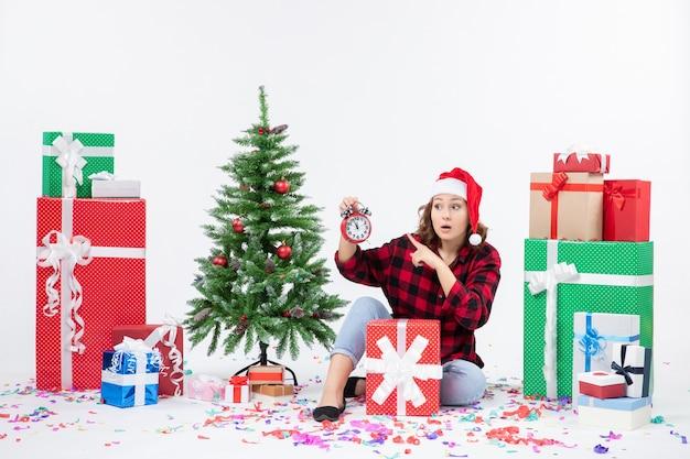 Widok z przodu młodej kobiety siedzącej wokół świątecznych prezentów, trzymając zegary na białej ścianie