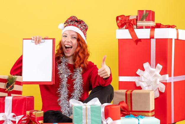 Widok z przodu młodej kobiety siedzącej wokół świątecznych prezentów z notatką pliku na żółtej ścianie