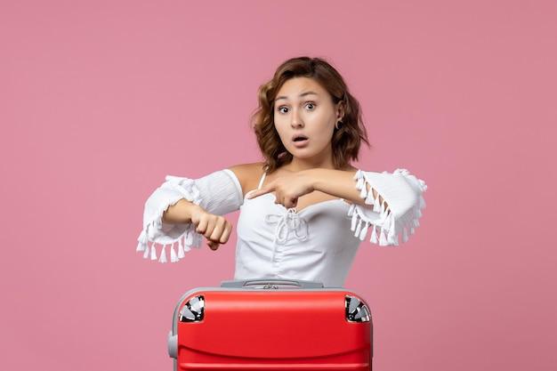 Widok z przodu młodej kobiety sprawdzającej czas z czerwoną torbą wakacyjną na różowej ścianie