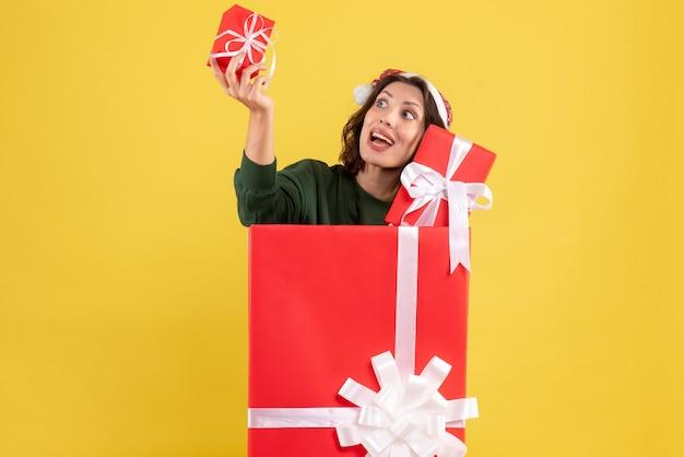 Widok z przodu młodej kobiety stojącej wewnątrz pudełka z prezentami xmas na żółtej ścianie