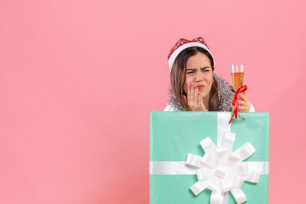 Widok z przodu młodej kobiety świętującej boże narodzenie przy drinku na różowej ścianie
