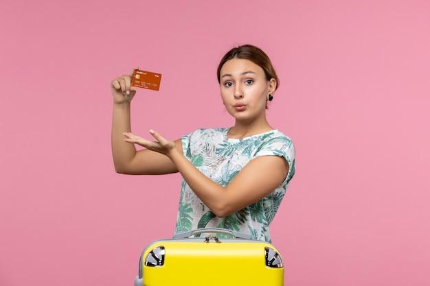 Widok z przodu młodej kobiety trzymającej brązową kartę bankową na różowej ścianie