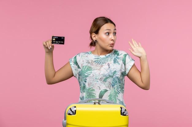 Widok z przodu młodej kobiety trzymającej czarną kartę bankową na różowej ścianie