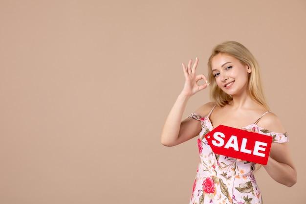 Widok z przodu młodej kobiety trzymającej czerwoną tablicę sprzedażową na jasnobrązowej ścianie