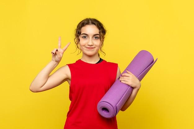 Widok z przodu młodej kobiety trzymającej fioletowy dywan na żółtej ścianie