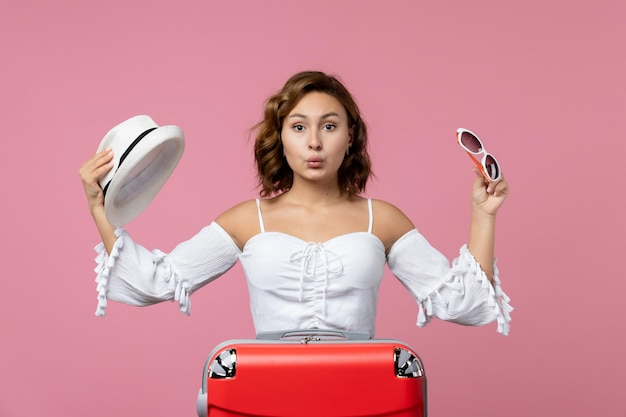 Widok z przodu młodej kobiety trzymającej kapelusz i okulary przeciwsłoneczne z czerwoną torbą na różowej ścianie