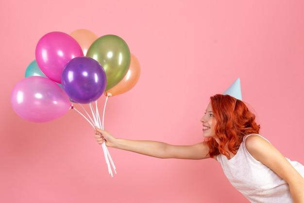Widok z przodu młodej kobiety trzymającej kolorowe balony na różowej ścianie