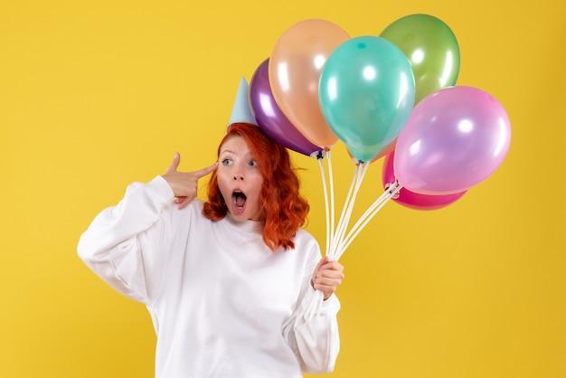 Widok z przodu młodej kobiety trzymającej kolorowe balony na żółtej ścianie