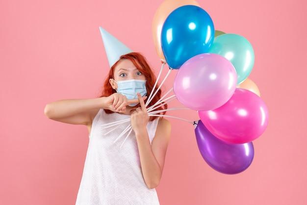 Widok z przodu młodej kobiety trzymającej kolorowe balony w sterylnej masce na różowej ścianie