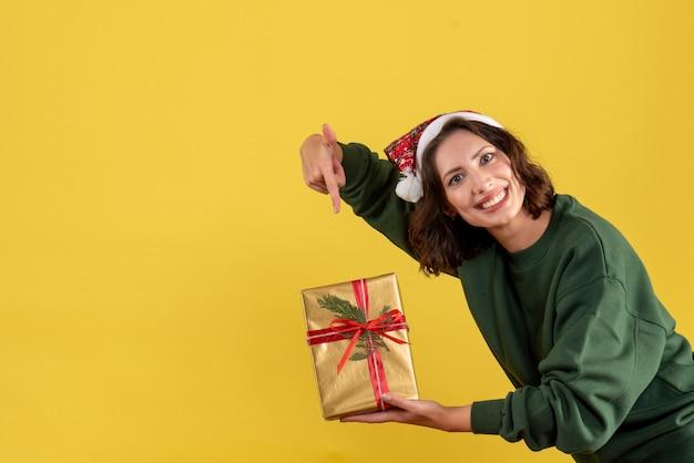 Widok z przodu młodej kobiety trzymającej mały prezent gwiazdkowy na żółtej ścianie