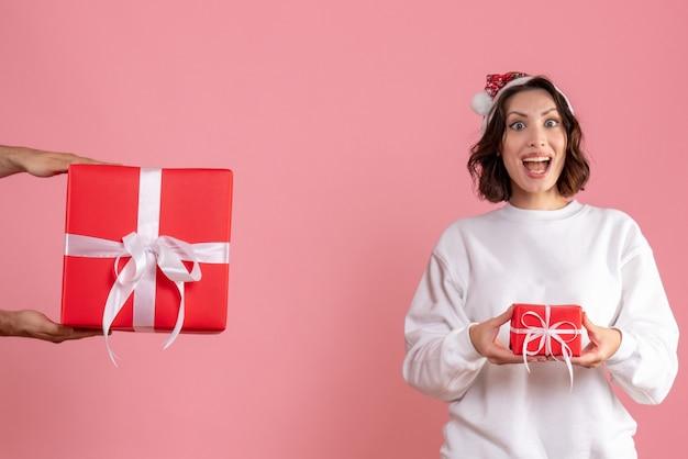Widok z przodu młodej kobiety trzymającej mały prezent i nie przyjmującej prezentu od mężczyzny na różowej ścianie