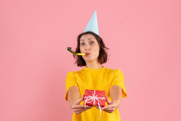 Widok z przodu młodej kobiety trzymającej mały prezent na różowej ścianie