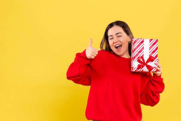 Widok z przodu młodej kobiety trzymającej mały prezent na żółtej ścianie