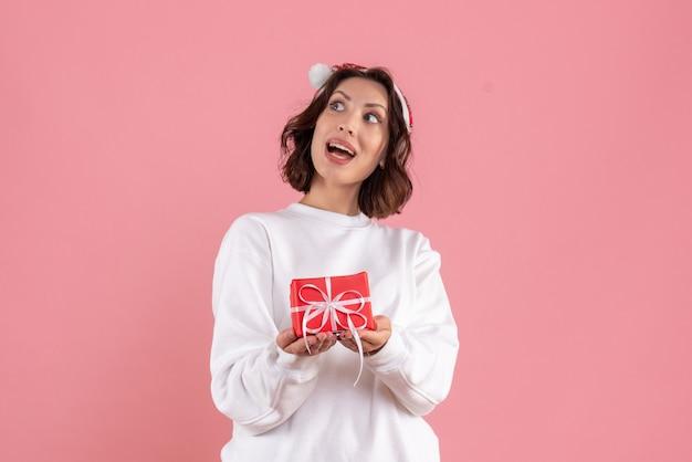 Widok z przodu młodej kobiety trzymającej mały prezent świąteczny na różowej ścianie
