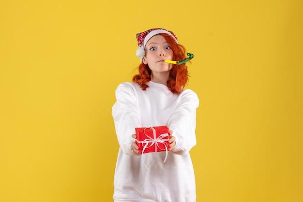 Widok z przodu młodej kobiety trzymającej mały prezent xmas na żółtej ścianie