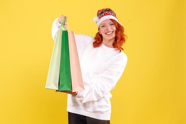 Widok z przodu młodej kobiety trzymającej paczki z zakupów na żółtej ścianie