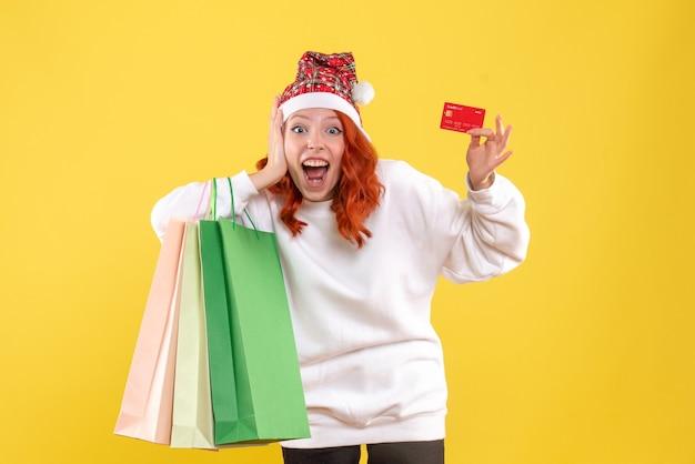 Widok z przodu młodej kobiety trzymającej pakiety zakupów i karty bankowej na żółtej ścianie