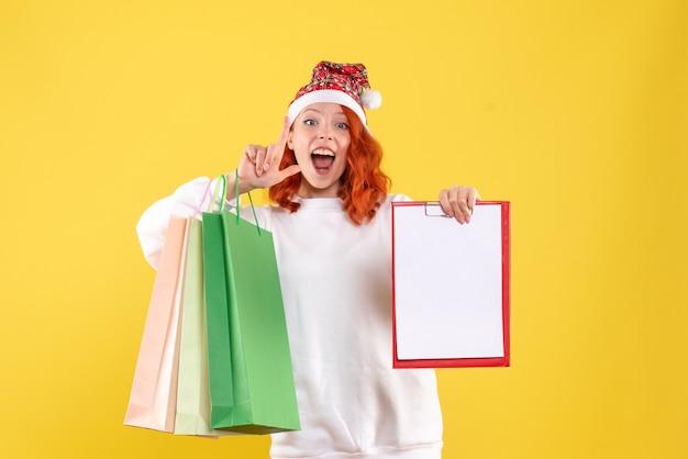 Widok z przodu młodej kobiety trzymającej pakiety zakupów na żółtej ścianie