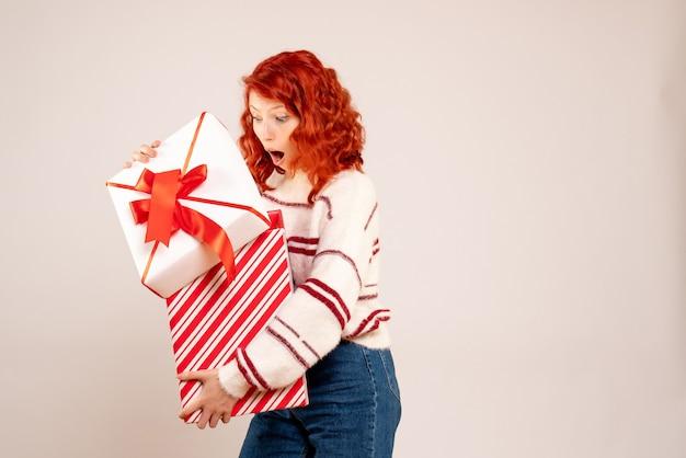 Widok z przodu młodej kobiety trzymającej prezent gwiazdkowy na białej ścianie