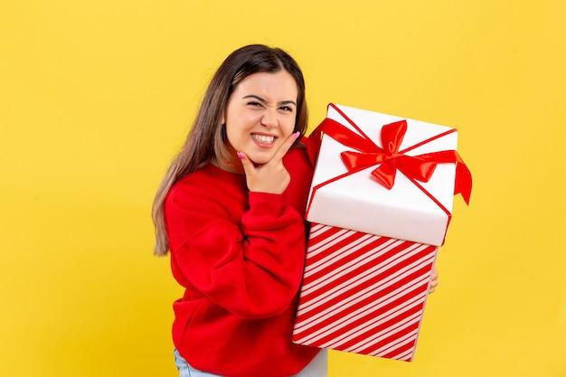 Widok z przodu młodej kobiety trzymającej prezent świąteczny w pudełku na żółtej ścianie