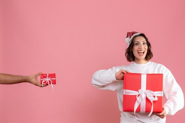 Widok z przodu młodej kobiety trzymającej prezent z mężczyzną, który daje jej inny prezent na różowej ścianie